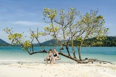 Madre e hijo que se sientan en un oscilación en la playa idílica Foto de archivo