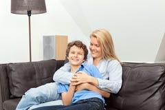 Madre e hijo que se sientan en un sofá Foto de archivo libre de regalías