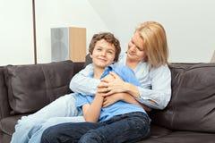 Madre e hijo que se sientan en un sofá Fotografía de archivo libre de regalías