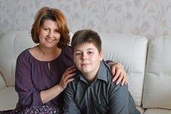 Madre e hijo que se sientan en un sofá en sitio Fotos de archivo