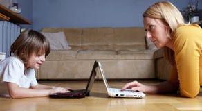 Madre e hijo que trabajan en dos pequeñas computadoras portátiles Foto de archivo libre de regalías