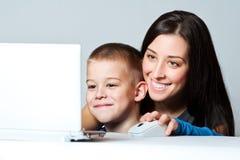 Madre e hijo que trabajan usando la computadora portátil Foto de archivo
