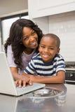 Madre e hijo que usa la computadora portátil Fotografía de archivo