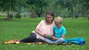 Madre e hijo que usa la tableta en el parque, acceso a internet inalámbrico dondequiera almacen de metraje de vídeo