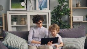 Madre e hijo que usa la tableta que mira la pantalla y que habla en el sofá en casa acogedora almacen de metraje de vídeo
