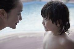 Madre e hijo sonrientes cara a cara por la piscina Foto de archivo libre de regalías