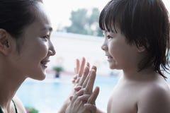 Madre e hijo sonrientes cara a cara y llevar a cabo las manos por la piscina Foto de archivo libre de regalías