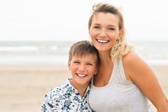 Madre e hijo sonrientes felices en la playa Imagenes de archivo