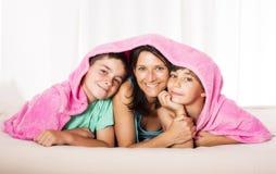 Madre e hijos en cama Imágenes de archivo libres de regalías