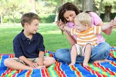 Madre e hijos que juegan en parque Imagenes de archivo