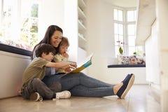 Madre e hijos que leen historia en casa junto imagen de archivo libre de regalías