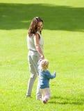 Madre e neonata che camminano sull'erba Immagini Stock Libere da Diritti