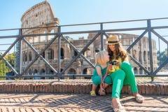 Madre e neonata che si siedono davanti al colosseum Fotografia Stock