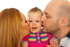 Madre e padre che baciano bambino Fotografia Stock Libera da Diritti
