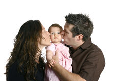 Madre e padre che baciano bambino sveglio fotografia stock