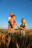 Madre e padre con il bambino sulle spalle su frumento Fotografie Stock