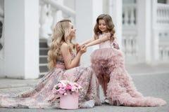 Madre e piccola figlia in abiti di palla rosa all'aperto di estate vicino al palazzo fotografia stock