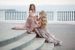 Madre e piccola figlia in abiti di palla rosa all'aperto di estate vicino al palazzo fotografia stock libera da diritti