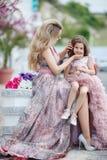 Madre e piccola figlia in abiti di palla rosa all'aperto di estate vicino al palazzo immagine stock