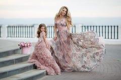 Madre e piccola figlia in abiti di palla rosa all'aperto di estate vicino al palazzo immagine stock libera da diritti