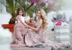 Madre e piccola figlia in abiti di palla rosa all'aperto di estate vicino al palazzo immagini stock