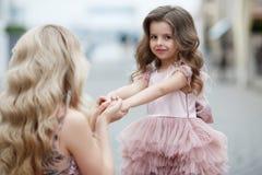 Madre e piccola figlia in abiti di palla rosa all'aperto di estate vicino al palazzo fotografie stock libere da diritti