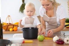 Madre e piccola figlia che cucinano nella cucina Spendendo tempo tutto insieme o concetto 'nucleo familiare' felice Fotografie Stock Libere da Diritti