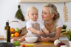 Madre e piccola figlia che cucinano nella cucina Spendendo tempo tutto insieme o concetto 'nucleo familiare' felice Fotografia Stock