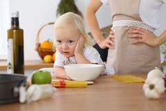 Madre e piccola figlia che cucinano nella cucina Spendendo tempo tutto insieme o concetto 'nucleo familiare' felice Immagini Stock Libere da Diritti