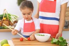 Madre e piccola figlia che cucinano prima colazione saporita di insalata fresca Pomodori d'affettatura e mescolantesi del piccolo immagini stock