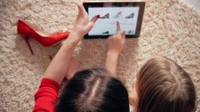 Madre e piccola figlia che esaminano calzature mentre comperando online sulla compressa digitale Il concetto di acquisto online stock footage