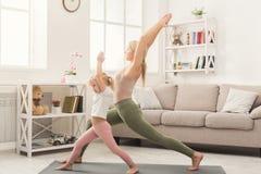 Madre e piccola figlia che fanno insieme yoga Immagini Stock Libere da Diritti