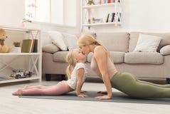 Madre e piccola figlia che fanno insieme yoga Fotografia Stock