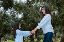 Madre e piccola figlia che si tengono per mano divertendosi in un parco fotografia stock