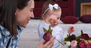 Madre e piccola figlia che sistemano i fiori rosa stock footage