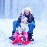 Madre e piccola figlia sveglia del bambino divertendosi su una slitta i Fotografie Stock