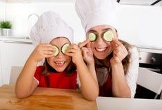 Madre e piccolo derivato in cappello del cuoco e grembiule che gioca con le fette del cetriolo sugli occhi in cucina Fotografia Stock Libera da Diritti