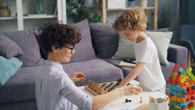 Madre e piccolo figlio che dispongono i pezzi degli scacchi sulla scacchiera che gioca a casa alla tavola stock footage