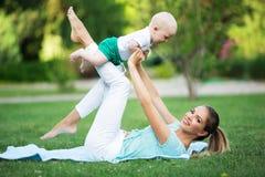 Madre e piccolo figlio che fanno esercizio all'aperto Stile di vita sano yoga Fotografia Stock