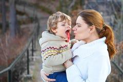 Madre e piccolo figlio in parco o in foresta, all'aperto Abbracciare e divertiresi insieme Ragazzo felice del bambino e giovane m fotografia stock libera da diritti