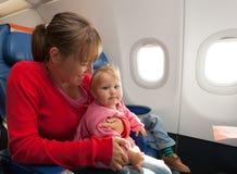 Madre e piccolo viaggio della figlia in aereo fotografia stock