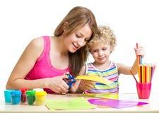 Madre e pittura e taglio del bambino fotografia stock libera da diritti