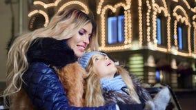 Madre e poca neonata che parlano godendo della festa di Natale alla decorazione che illumina fondo stock footage