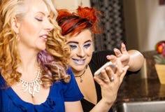 Madre e telefono dai capelli rossi della parte della figlia immagine stock
