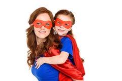 madre eccellente che trasporta sulle spalle figlia adorabile in maschera e mantello e che sorride alla macchina fotografica immagine stock libera da diritti