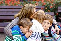 Madre ed abbracciare di tre bambini Seduta felice della famiglia all'aperto: donna e due bambini svegli del ragazzo dei bambini d immagini stock