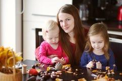 Madre ed i suoi bambini che fanno le creature delle castagne Fotografie Stock