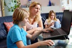 Madre ed i suoi bambini che per mezzo del computer immagine stock libera da diritti