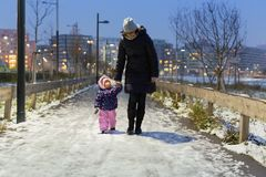 Madre ed il suo piccolo bambino che camminano nel parco nevoso nell'inverno fotografia stock libera da diritti