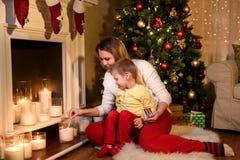 Madre ed suo figlio che accendono le candele bianche fotografia stock